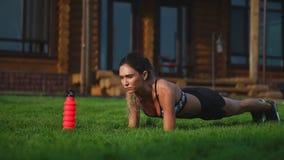 Muchacha apta que hace el ejercicio del tablón al aire libre en el día de verano caliente del parque Concepto de resistencia y de metrajes
