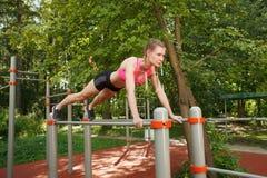 Muchacha apta que hace pectorales del ejercicio en las barras de deportes al aire libre Fotografía de archivo libre de regalías