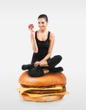 Muchacha apta que se sienta en una hamburguesa que sostiene una manzana Foto de archivo libre de regalías