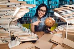Muchacha asiática étnica rodeada por los libros en biblioteca en la noche El estudiante está utilizando el globo fotos de archivo libres de regalías