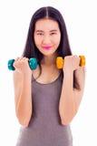 Muchacha asiática adolescente que lleva a cabo pesas de gimnasia Fotos de archivo libres de regalías