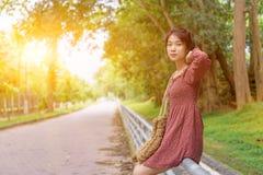 Muchacha asiática adolescente que se sienta solamente el día de verano Jóvenes tristes solos Foto de archivo