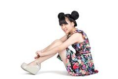 Muchacha asiática adolescente sonriente que se sienta en el piso Foto de archivo