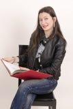 Muchacha asiática agradable en chaqueta negra con un libro rojo. Foto de archivo