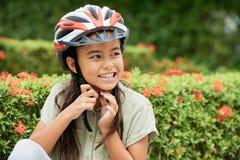 Muchacha asiática alegre que pone en casco fotografía de archivo
