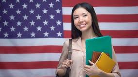 Muchacha asiática alegre que sonríe con los libros contra el fondo de la bandera de los E.E.U.U., educación almacen de metraje de vídeo