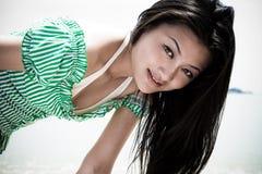 Muchacha asiática asoleada en verde Foto de archivo libre de regalías