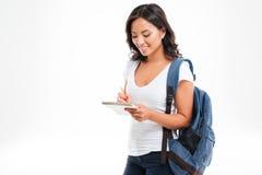 Muchacha asiática atractiva alegre con la mochila que hace notas en cuaderno Fotos de archivo libres de regalías