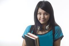 Muchacha asiática atractiva con los libros de escuela Imagenes de archivo