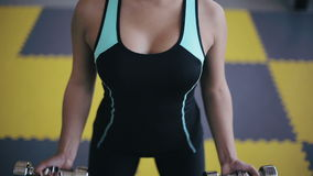Muchacha asiática atractiva joven que hace ejercicio con pesas de gimnasia metrajes