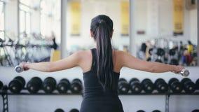 Muchacha asiática atractiva joven que hace ejercicio con pesas de gimnasia almacen de video