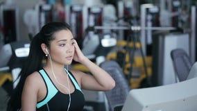 Muchacha asiática atractiva que corre en la rueda de ardilla en el gimnasio con los auriculares Cara derecha del perfil almacen de video