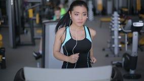 Muchacha asiática atractiva que corre en la rueda de ardilla en el gimnasio con los auriculares Retrato de la cara llena almacen de metraje de vídeo