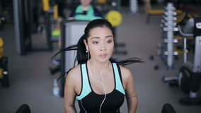 Muchacha asiática atractiva que corre en la rueda de ardilla en el gimnasio con los auriculares Retrato de la cara llena metrajes