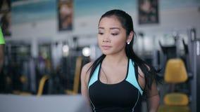 Muchacha asiática atractiva que corre en la rueda de ardilla en el gimnasio Izquierda 3/4 retrato de la cara metrajes