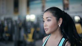 Muchacha asiática atractiva que corre en la rueda de ardilla en el gimnasio Izquierda 3/4 retrato de la cara almacen de metraje de vídeo