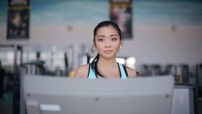 Muchacha asiática atractiva que corre en la rueda de ardilla en el gimnasio Retrato de la cara llena almacen de video