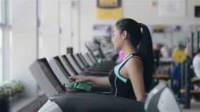 Muchacha asiática atractiva que corre en la rueda de ardilla en el gimnasio Tiro izquierdo de la cara del perfil almacen de video