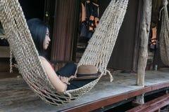 Muchacha asiática caucásica joven que balancea en una hamaca en una holgazanería agradable de una tarde del fin de semana Fotos de archivo libres de regalías