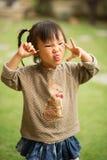 Muchacha asiática china de 5 años en un jardín que hace caras Imagenes de archivo