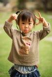 Muchacha asiática china de 5 años en un jardín que hace caras Fotos de archivo