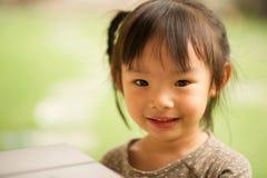 Muchacha asiática china de 5 años en una sonrisa del jardín Foto de archivo