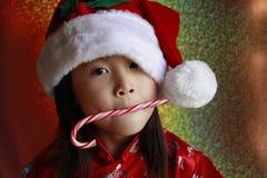 Muchacha asiática con el bastón de caramelo imagenes de archivo
