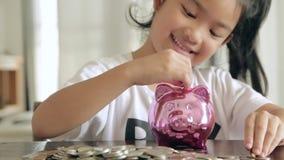 Muchacha asiática con el dinero del ahorro metrajes
