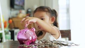 Muchacha asiática con el dinero del ahorro almacen de metraje de vídeo