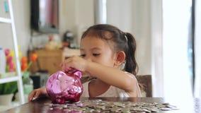 Muchacha asiática con el dinero del ahorro, concepto del depósito metrajes