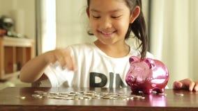 Muchacha asiática con el dinero del ahorro, depósito metrajes
