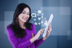 Muchacha asiática con el medios icono social en la tableta Fotos de archivo libres de regalías