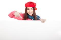 Muchacha asiática con el punto rojo del sombrero de la Navidad abajo para esconder la muestra Fotos de archivo