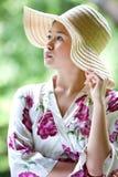 Muchacha asiática con el sombrero de paja ancho del borde en el parque Fotografía de archivo