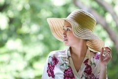 Muchacha asiática con el sombrero de paja ancho del borde en el parque Imagen de archivo