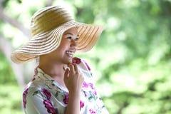 Muchacha asiática con el sombrero de paja ancho del borde en el parque Fotos de archivo libres de regalías