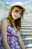 Muchacha asiática con el sombrero, sentándose en las escaleras Foto de archivo