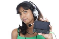 Muchacha asiática con el teléfono móvil y el auricular Imagen de archivo libre de regalías