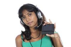Muchacha asiática con el teléfono móvil y el auricular Fotos de archivo