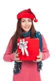 Muchacha asiática con la demostración roja del sombrero de la Navidad una caja de regalo Imagen de archivo