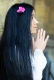 Muchacha asiática con la flor en sus pelos que ruega Fotografía de archivo