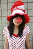 Muchacha asiática con la nariz y el sombrero rojos Foto de archivo