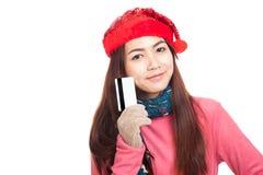 Muchacha asiática con la tarjeta de crédito roja de la demostración de la sonrisa del sombrero de la Navidad Imagen de archivo libre de regalías