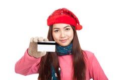 Muchacha asiática con la tarjeta de crédito roja de la demostración de la sonrisa del sombrero de la Navidad Fotografía de archivo libre de regalías