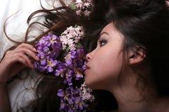 Muchacha asiática con las flores Fotos de archivo