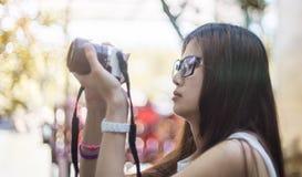 Muchacha asiática con los vidrios que toman una foto Imagenes de archivo