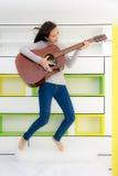 Muchacha asiática con salto de la guitarra en dormitorio Fotografía de archivo libre de regalías