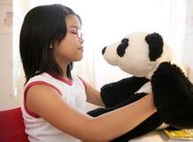 Muchacha asiática con su oso de peluche de la panda Foto de archivo