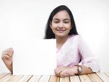 Muchacha asiática con una tarjeta en blanco Imágenes de archivo libres de regalías