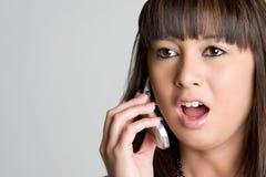 Muchacha asiática dada una sacudida eléctrica del teléfono Foto de archivo